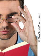 Closeup of a man in glasses reading a book