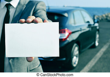 man in suit holding a blank signboard with a car in the backgrou