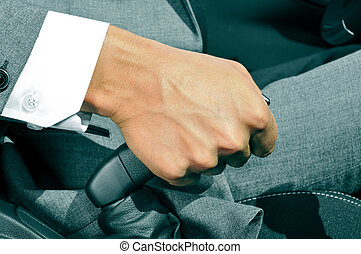 man in suit pulling the hand brake of a car - closeup of a...