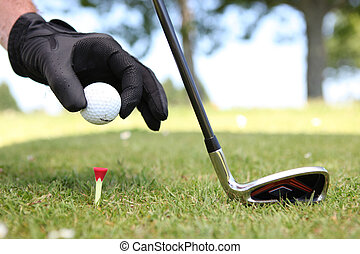 Closeup of a man placing a golf ball on the tee