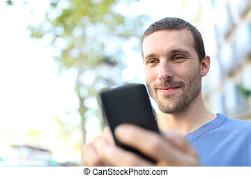 Closeup of a man using smart phone in the street