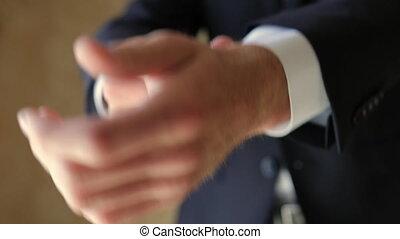 Closeup of A Man who Adjusts His Shirt Cufflinks