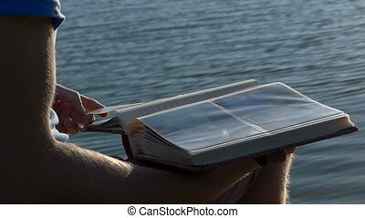 Closeup of a man who looks at his family photoalbum on a lake bank