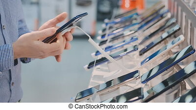 Closeup of a man's hand is choosing to buy a new smartphone near the storefront in an electronics store