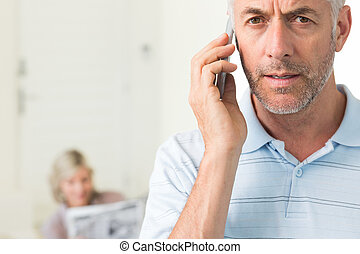 Closeup of a mature man using cellphone with woman reading newspaper in background at home
