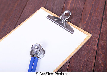 Closeup of a medical stethoscope with folder on wooden background