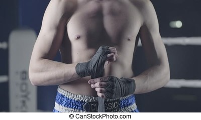 Closeup of a mixed martial arts fighter wrapping his hands...