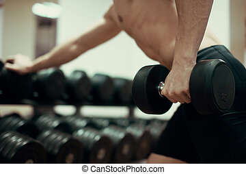 Closeup of a muscular young man lifting weights in gym.
