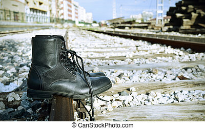 mens boots abandoned on the railroad tracks