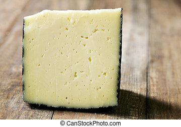 manchego cheese from Spain - closeup of a piece of manchego...
