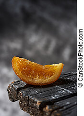 closeup of a piece of spanish candied orange on a rustic dark gray wooden surface, against a gray background