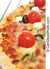 closeup of a pizza with bacon, olives, cherry tomatoes, goat cheese, green pepper and eggplant