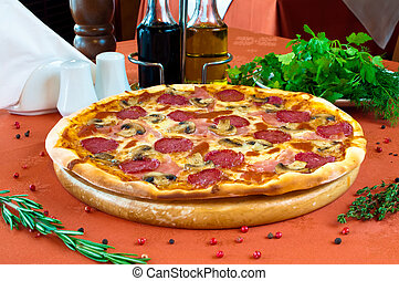 Closeup of a pizza with salami and mashrooms