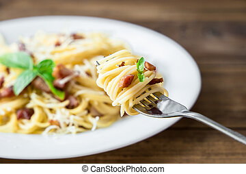 plate of Pasta Carbonara and Spaghetti with bacon and parmesan cheese on a fork on old wooden table