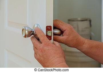 Closeup of a professional locksmith installing or repairing...