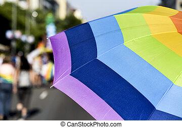 rainbow-patterned umbrella in a gay pride parade