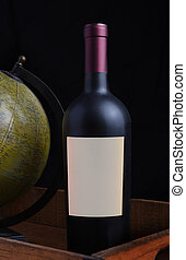 Closeup of a red wine bottle with a blank label in a wood crate with antique world gobe.