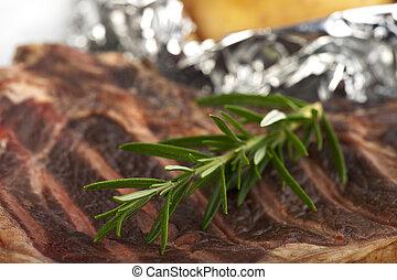 closeup of a rosemary leaf on a t-bone-steak