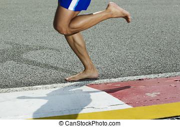 Closeup of a runners feet barefoot running