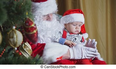 Closeup of a santa playing with a small child