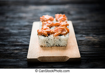 a set of sushi rolls with salmon topping on wooden board