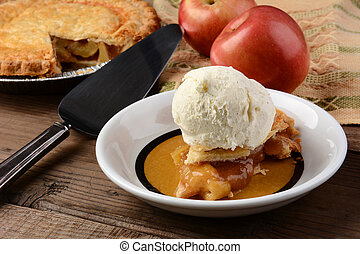 Closeup of a slice of Apple Pie a la Mode. Fresh Fuji apples and a whole pie are in the background. Horizontal format.