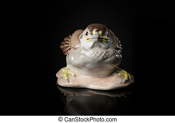 Closeup of a small porcelain sparrow standing on a reflective surface