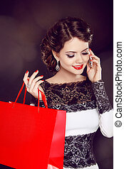 Closeup of a smiling beautiful young woman with shopping bag talking over the cellphone