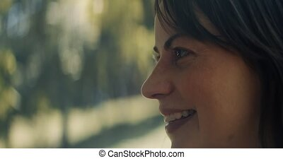 Closeup of a smiling woman at the park.