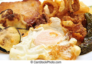 closeup of a spanish combo platter with fried egg, grilled pepper, fried calamares, breaded tenderloin and fried eggplant