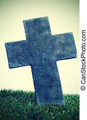 closeup of a stone cross of a grave in a cemetery for halloween