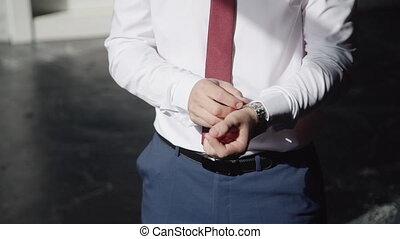 Closeup of a successful man putting on a wristwatch. Male's ...