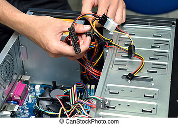 Closeup of a technician's hands wiring a computer mainboard