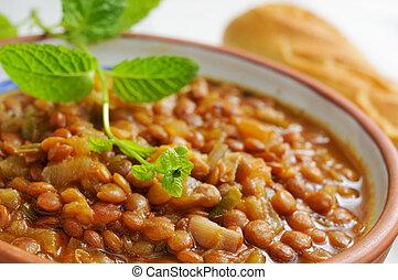 closeup of a vegan lentil stew on an earthenware bowl