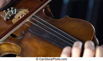 Closeup of a violin and a girl fingering the strings and bow. Black background