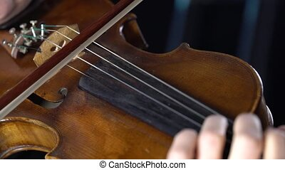 Closeup of a violin fingering the strings and bow. Black...