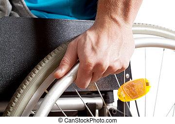 Closeup of a wheelchair, hand on a wheel