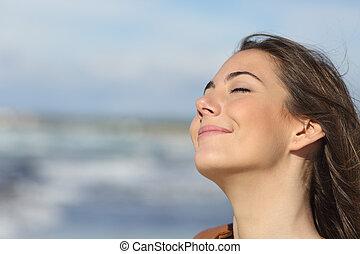 Closeup of a woman breathing fresh air on the beach -...