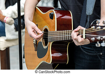 closeup of a woman hands playing acoustic guitar outdoors