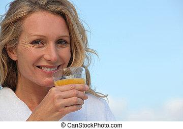 Closeup of a woman in a bathrobe drinking orange juice outdoors