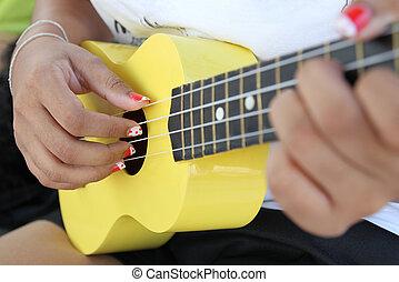 Closeup of a woman playing ukulele.