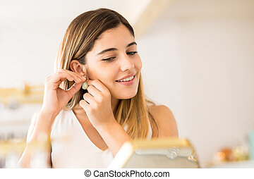 Closeup of a woman trying on some earrings