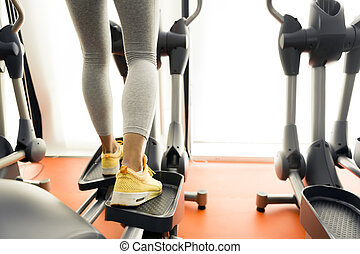 Closeup of a woman using a stepper and training in a gym -...