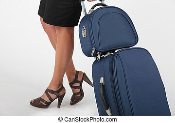 Closeup of a woman wheeling carry-on luggage