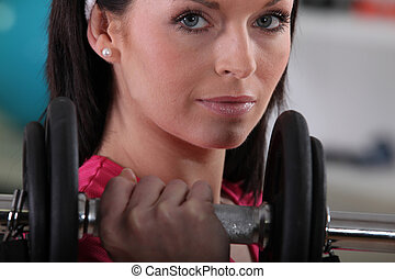 Closeup of a woman with a dumbbell
