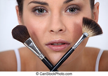 Closeup of a woman with makeup brushes