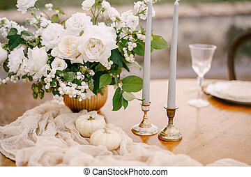Closeup of a wooden table decorated for a wedding dinner.