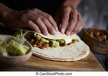 closeup of a young caucasian man preparing a durum or a burrito, with chicken meat cooked with different vegetables such as onion or red and green pepper, and fresh lettuce and raw cucumber