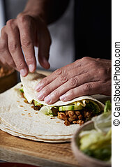 closeup of a young caucasian man preparing a durum or a burrito, with chicken meat, lettuce and cucumber