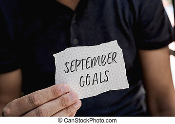 man with a note with the text september goals